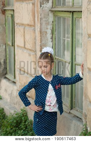cute little girl in a fashionable costume is standing by the old house with wooden windows