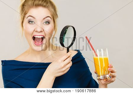Woman Holding Magnifying Glass Investigating Juice