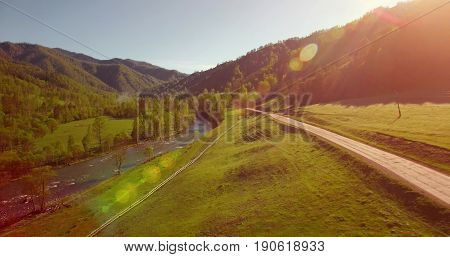 Aerial UHD 4K view. Mid-air flight over fresh mountain river and meadow at sunny summer morning. Green trees and sun rays on horizon. Rural dirt road below.