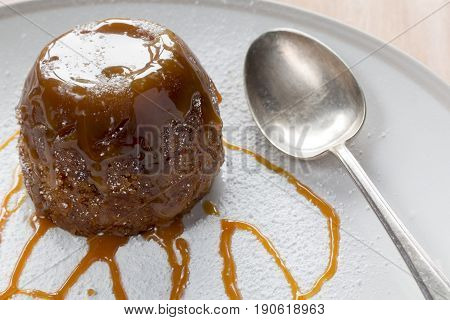 Sticky toffee pudding on a white sugar dusted plate drizzled with caramel sauce with a spoon
