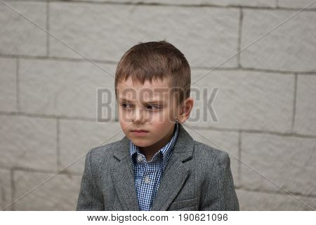 Portrait of a small boy in a jacket and shirt on a wall background