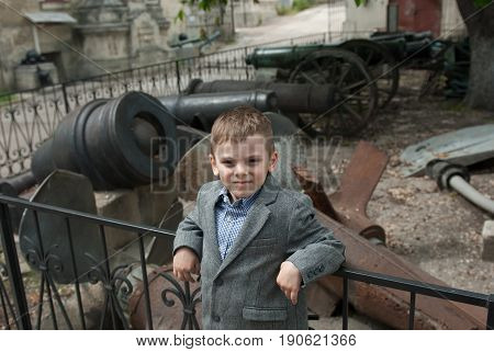 one caucasian little boy wearing jacket and shirt in a naval museum with guns and propellers on the background