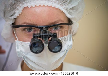 Young female Doctor wearing dental loupe binoculars, headshot portrait.