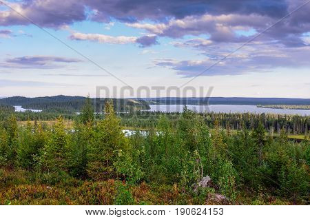 A bright natural landscape in summer season. A view from hill over the forest bog and lakes in northern Finland.