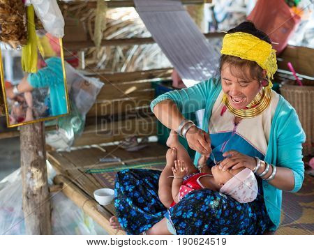 CHIANG RAI, THAILAND - FEBRUARY 4, 2016: Karen long neck woman feeding a kid in a village between Chiang Rai and Chiang Mai. Karen is one of several ethnic hill tribes in northern Thailand.