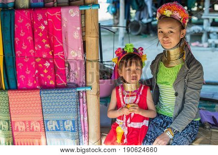 CHIANG RAI, THAILAND - FEBRUARY 4, 2016: Karen long neck mother with girl child in a village between Chiang Rai and Chiang Mai. Karen is one of several ethnic hill tribes in northern Thailand.