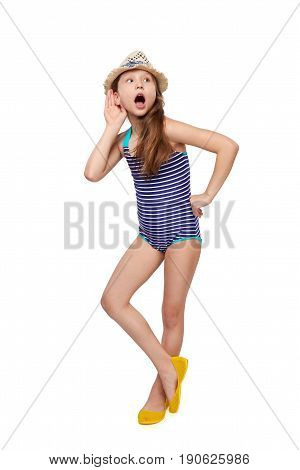Surprised full length child girl in swimsuit and summer hat with hand on ear listening, over white background