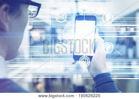 Young businessman in glasses holding empty white cellular phone with digital pattern. Mock up Media concept