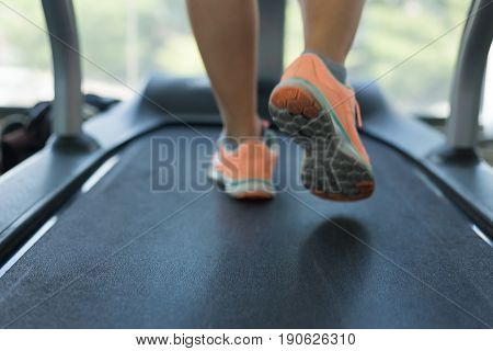 close-up floor treadmill machine human jogging exercise on run cardio equipment at sport healthy club center