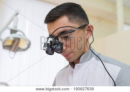 Portrait of Young doctor with dental binocular loupes on his face at dentist clinic