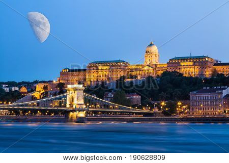 Budapest during blue hour - Szechenyi Chain Bridge, that spans the River Danube between Buda and Pest and Buda Castle with moon in the sky.