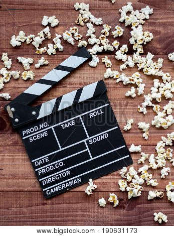 Vintage Classic Clapperboard And Popcorn On Brown Wooden Table