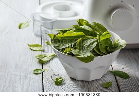 Fresh spinach leaves in white bowl and blender on white wooden background