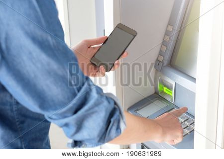 Man using his credit card in an atm for cash withdrawal holding smart-phone
