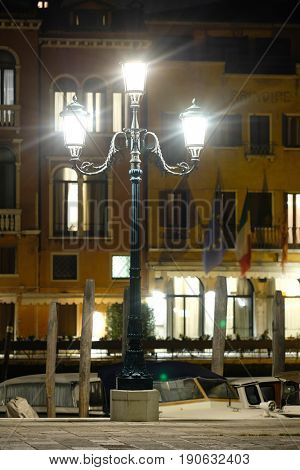 Venice, Italy, May, 31, 2017: lamp on a channel embankment at night in Venice, Italy