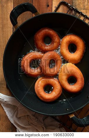 Sweet ruddy donuts with sugar icing in a frying pan