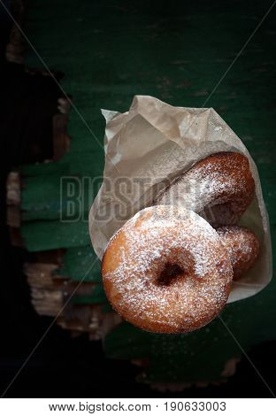 Sweet ruddy donuts with sugar icing on a dark background
