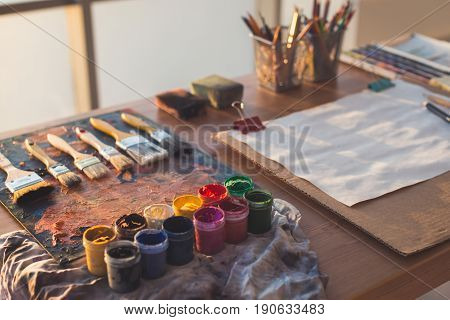 Painter workplace. Palette with brushstrokes and paintbrushes. Colorful gouache, crayons sets.
