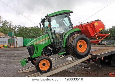 Tractor offloading from a truck after transportation