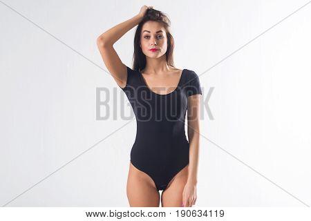 Cute brunette female model posing, wearing black one piece underwear suit, touching her hair.
