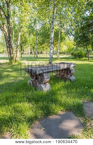 Old handmade wooden bench standing on lawn near white birch in the park or garden from the left of sandstone footpath.