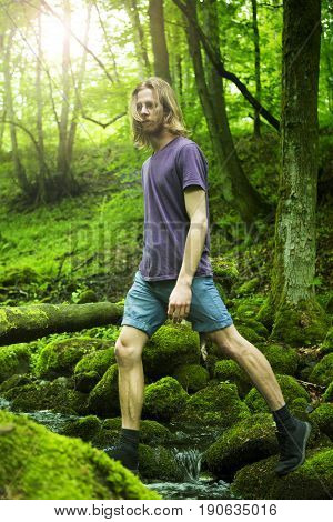 young red-haired man crossing a creek in green forest
