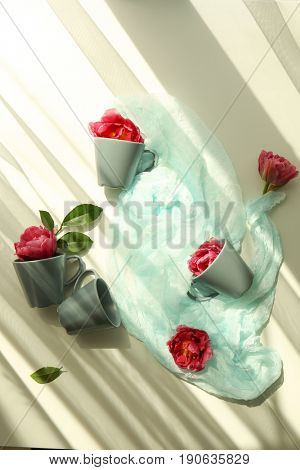 Composition of beautiful tulips and cups on light background