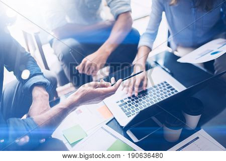 Closeup view of Teamwork process.Young coworkers work with new startup project in office.Analyze document, plans.Modern laptop on wood table, papers, documents.Horizontal, cropped