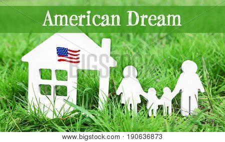 Text AMERICAN DREAM with models of house and family on green grass, closeup