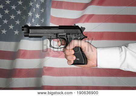 Man holding firearm and American flag on background. Gun control concept