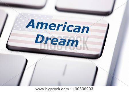 Text AMERICAN DREAM and USA flag on keyboard button, closeup