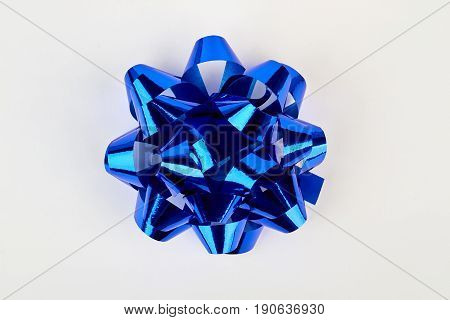 Blue bow for gift box. Bright bow on white, top view.