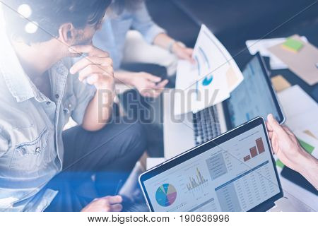Closeup view of Group of young coworkers working together in modern office studio.Business people discussing new startup project.Horizontal, blurred background