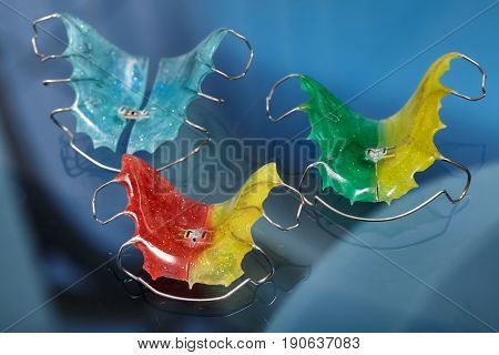 Colorful dental braces or retainers for teeth on blue glass background closeup