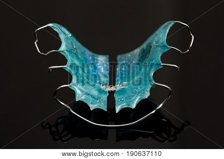 Colorful dental braces or retainers for teeth on black glass background closeup