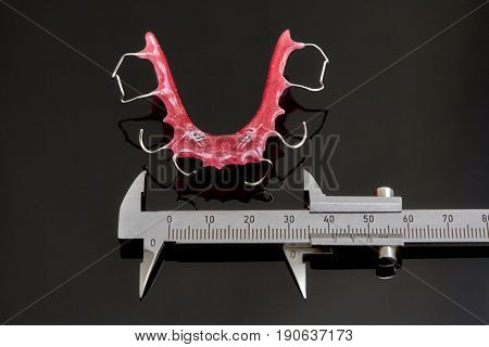 Colorful dental braces or retainers for teeth on black glass background and vernier caliper closeup