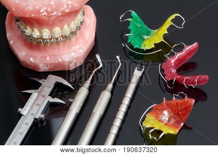 Human jaw or teeth model with dental braces and dentist tools and retainers