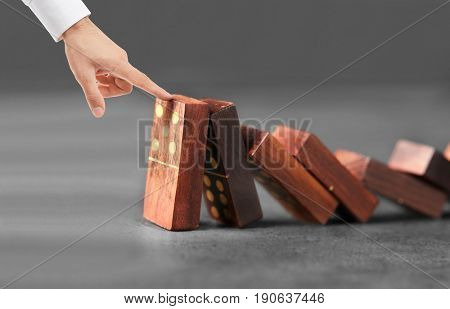 Man trying to stop falling dominoes on gray background. Leadership concept