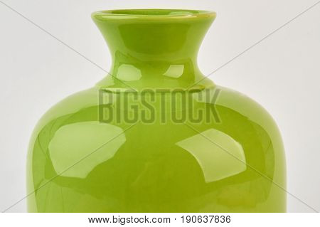 Cropped image of green vase. Ceramic pottery on white background. Decorate house with bright vase.