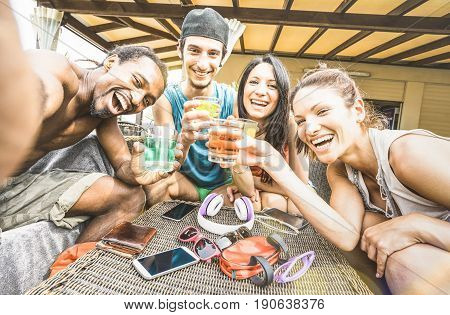 Multiracial happy friends group taking selfie and having drunk fun with cocktail at beach resort - Summer concept and multi ethnic friendship at bar restaurant - Sunny afternoon filtered color tones
