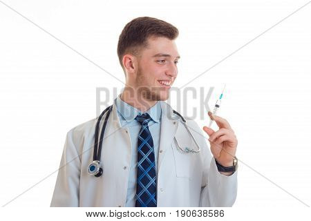 a young doctor in uniform with a gun in the hands of smiling isolated on white background