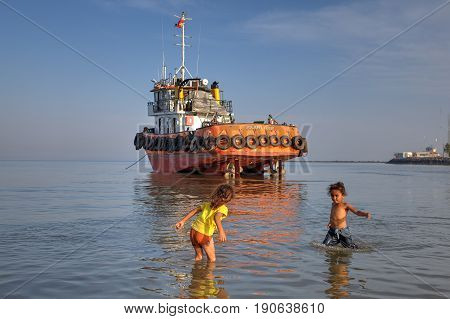Bandar Abbas Hormozgan Province Iran - 16 april 2017: Two little girls about seven years old play in the water near the shore against the background of an industrial boat that ran aground.