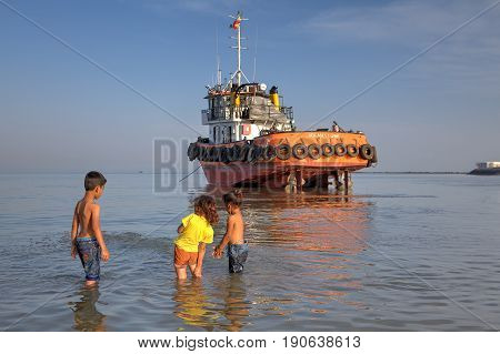 Bandar Abbas Hormozgan Province Iran - 16 april 2017: Three young children about 7 years old two little girls and one boy playing in the water of the Persian Gulf near the jammed boat.