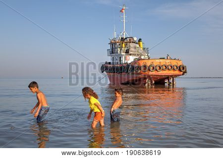 Bandar Abbas Hormozgan Province Iran - 16 april 2017: Children play in the water in the shallow waters of the Persian Gulf not far from an industrial boat that has run aground.
