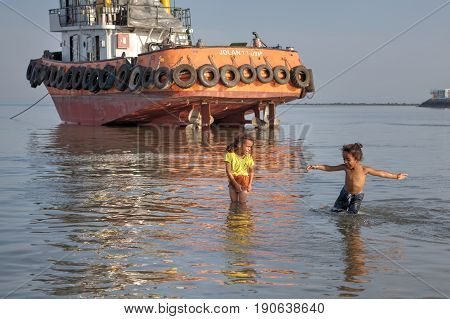 Bandar Abbas Hormozgan Province Iran - 16 april 2017: Two small Iranian girls about seven years old are walking along shallow water in the Persian Gulf not far from an abandoned towboat.