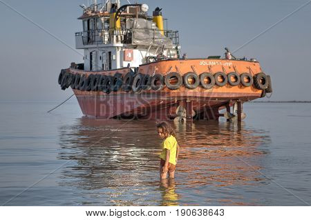 Bandar Abbas Hormozgan Iran - 16 april 2017: One little Iranian girl in a yellow T-shirt about seven years old walks on water in shallow waters of Persian Gulf near an aground industrial boat.