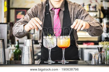 Classic bartender serving gin tonic and tequila sunrise with straw on drink glasses cups at fashion cocktail bar - Food and beverage concept with professional barman working at mixology restaurant