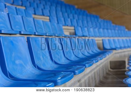 blue plastic seats in a sports hall in a row