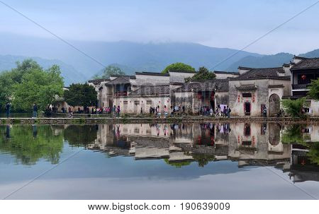 HONGCUN, CHINA - APRIL 20, 2014: Tourist walking around Moon Lake in Hongcun Village. Hongcun is ancient village in Anhui Province near the southwest of Mount Huangshan.