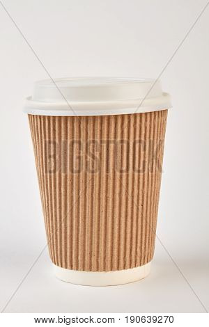 Coffee cardboard cup isolated. Brown disposable cup close up.